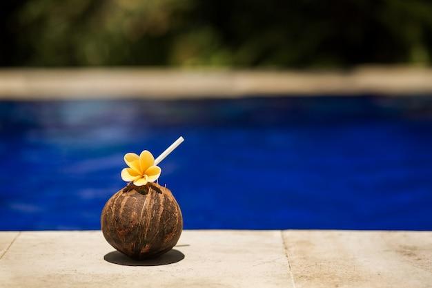 スイミングプールの端にある黄色い花のトロピカルココナッツドリンク。ホテルのリラックス Premium写真