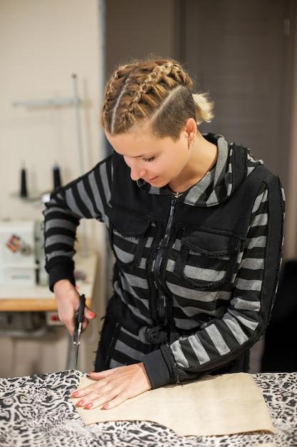 服の若い女の子デザイナー、彼のワークショップで服を作成するためにパターンで生地をカット Premium写真