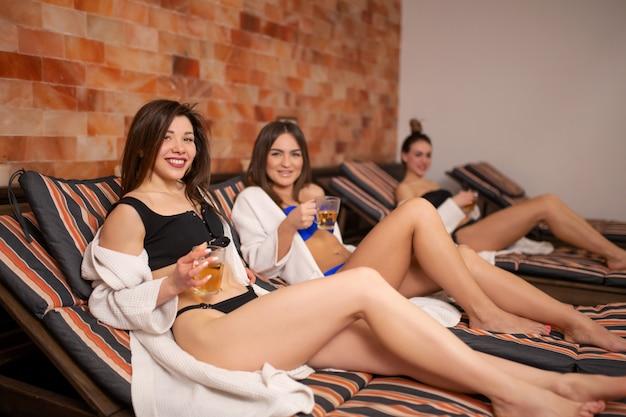 Группа молодых девушек отдыхает на деревянной палубе в сауне. веселиться в женской компании Premium Фотографии