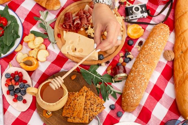 Женщина капает мед на бутерброд с пармой и сыром на открытом пикнике Premium Фотографии