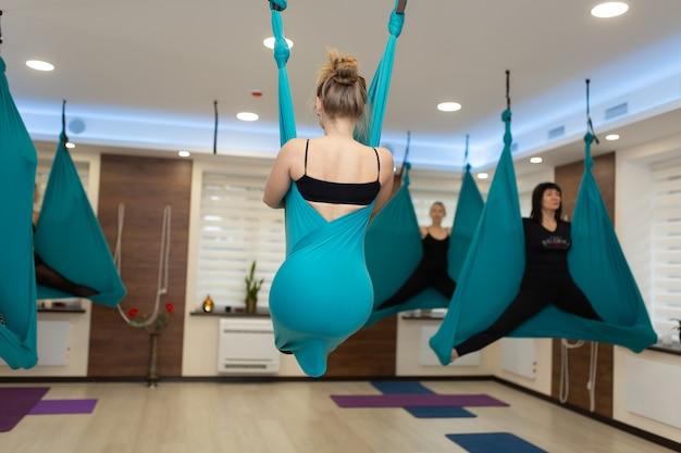 ハンモックでストレッチストレッチヨガをやっている女性。フィット感と健康のライフスタイル。 Premium写真