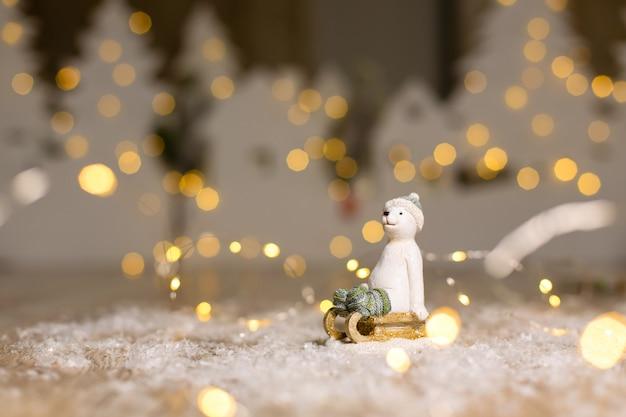 Декоративные статуэтки на рождественские темы. статуэтка белого медведя сидит на деревянных санях, в вязаной шапке и носках. Premium Фотографии