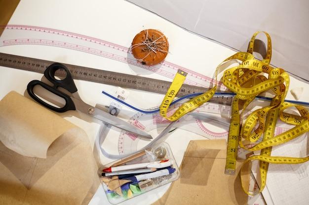 センチメートルの黄色、はさみ、定規、仕立て屋の他のツールの平面図 Premium写真