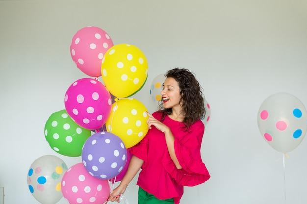 色の風船を持つ美しいかわいい陽気な女の子。休日お誕生日おめでとう。 Premium写真
