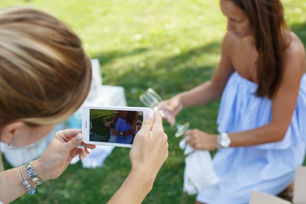 ピクニックの準備をしながら彼女は電話で電話で写真を撮る Premium写真