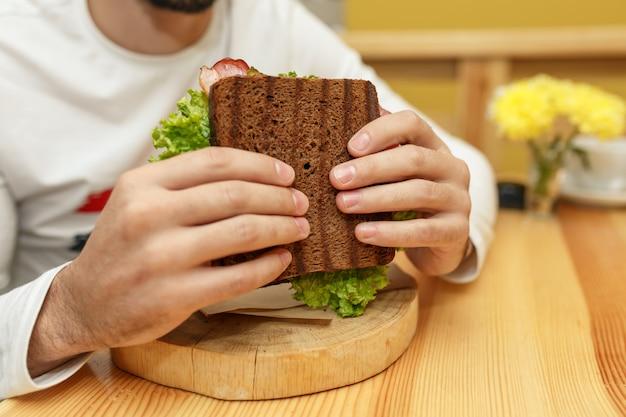 食欲をそそる空腹の若い男がサンドイッチを食べる Premium写真