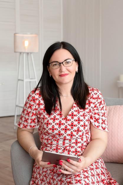 彼の手と笑顔でタブレットと明るいオフィスに座っている眼鏡の専門医師心理学者 Premium写真