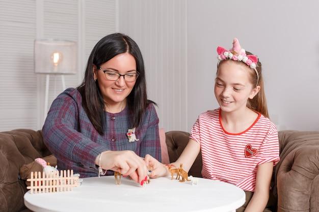 Мама и дочка проводят время вместе, сидят на диване, общаются и играют с игрушечными животными Premium Фотографии