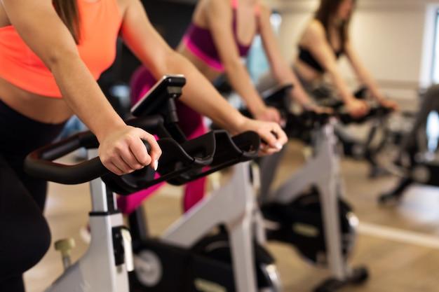 ジムでエアロバイクで若いスリムな女性トレーニングのグループ。スポーツとウェルネスのライフスタイルコンセプト Premium写真