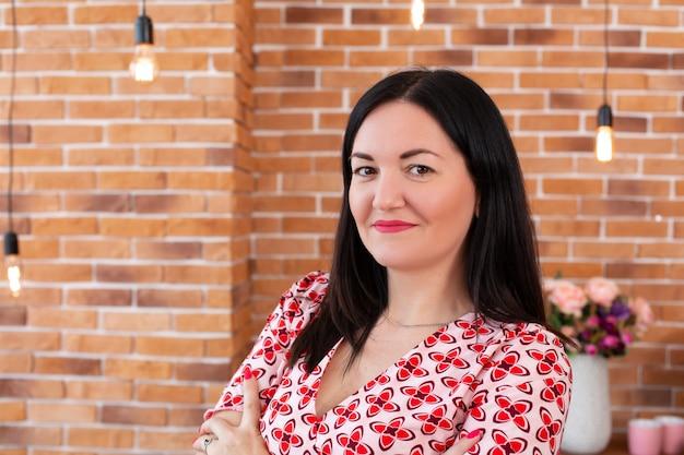 メガネの専門のかかりつけ医心理学者はロフトスタイルでオフィスに座って、カメラに笑顔します。心理療法。女性心理療法士の肖像 Premium写真