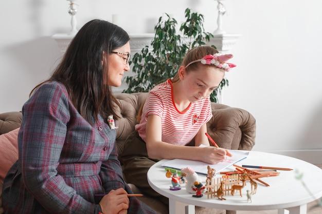 Мама и дочка проводят время вместе, садятся на диван, разговаривают и рисуют цветными карандашами. досуг мам и дочек. девушка рисует на бумаге Premium Фотографии