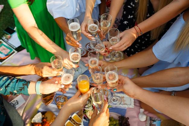 乾杯めがね食事屋外ピクニック食事を持つ人々のグループ Premium写真