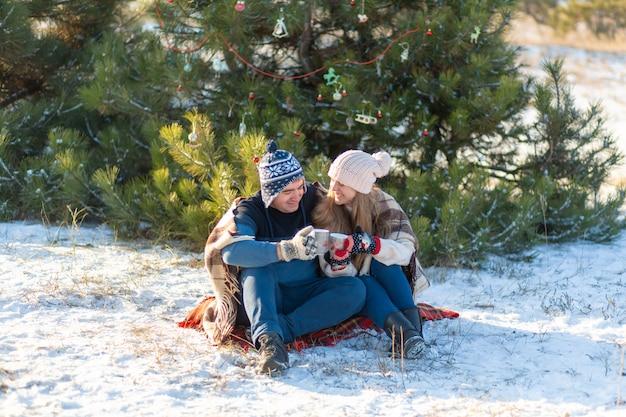 愛の若いカップルは、マシュマロと一緒に温かい飲み物を飲み、冬の森に座って、暖かく快適なラグに隠れて、自然を楽しみます。彼らは話し、森で熱い飲み物を飲みながら笑います Premium写真