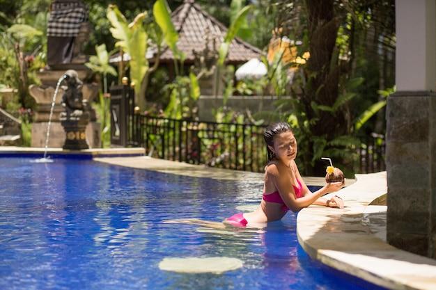 バカンススイミングプールでココナッツを飲むピンクの水着でセクシーな若い女性。 Premium写真