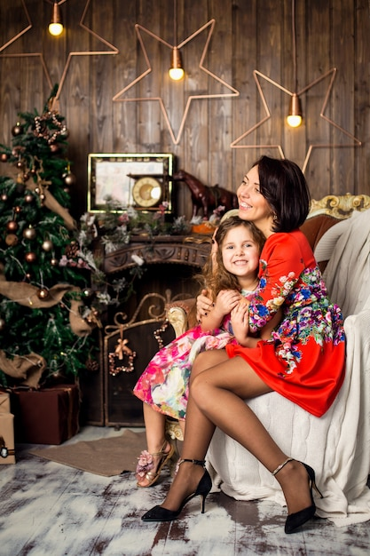 Семья празднует рождество. счастливая мать с дочерью в волшебную ночь. мама обнимает дочь. счастливого рождества и счастливых праздников. нежность, забота и взаимопонимание. Premium Фотографии