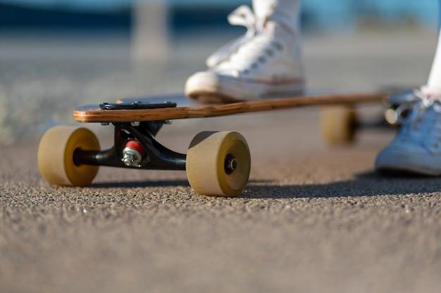 極端な面白い彼女の木製のロングボードスケートボードに乗って休んで白いスニーカーで女性の足のクローズアップ Premium写真