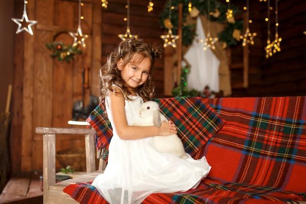 白いウサギとベンチに座っている白いドレスの少女 Premium写真