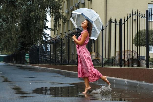 水たまりに雨の中で踊る透明な傘と赤いドレスの少女 Premium写真