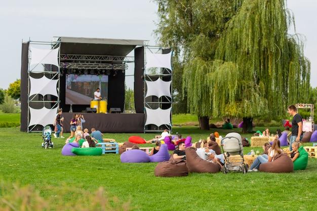 映画の日。人々は通りで大きなスクリーンで映画を見て、緑の芝生の上に座り、快適なバッグに入れて Premium写真