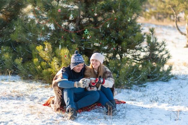 愛の若いカップルは、マシュマロと一緒に温かい飲み物を飲み、森の中で冬に座って、暖かく快適なラグに隠れて、自然を楽しみます Premium写真