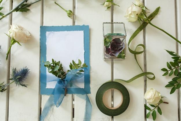 Свежие белые розы и свадебные приглашения на белом деревянном столе. оформление живых цветов Premium Фотографии