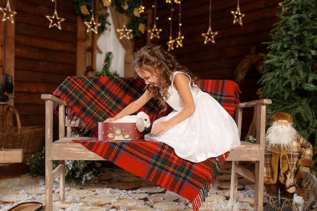 白いウサギのベンチとオープンボックスに座っている白いドレスの少女。夜のクリスマスツリーのインテリアの魔法の光 Premium写真