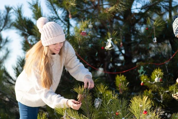女性は、森の冬の路上で装飾的なおもちゃや花輪で新年の緑の木を飾ります。クリスマスツリーの飾り Premium写真