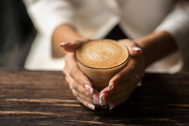 美しいマニキュアのクローズアップと女性の手は、木製のテーブルにホットコーヒーのカップを保持します。 Premium写真