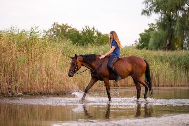 浅い湖で馬に乗る少女。 Premium写真