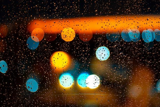 Капля воды на окнах и боке города на закате Premium Фотографии