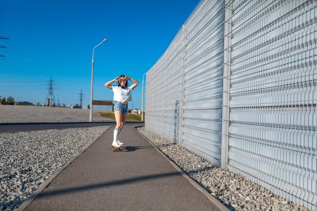 Стильная девушка в белых чулках катается по лонгборду по улице и слушает музыку. Premium Фотографии
