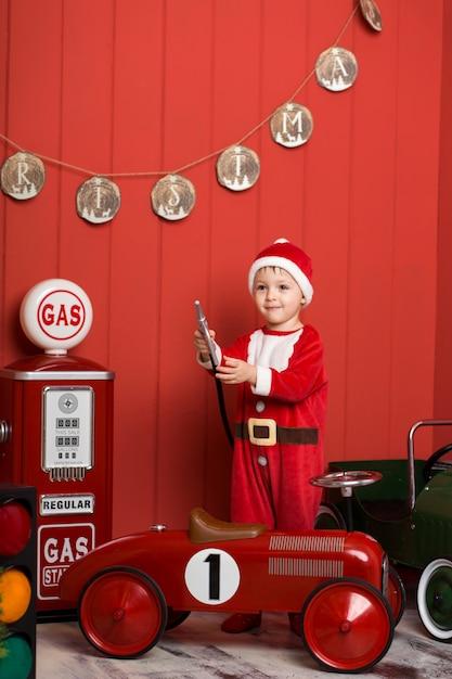 サンタクロースの衣装の少年はおもちゃの赤い車に乗る。 Premium写真