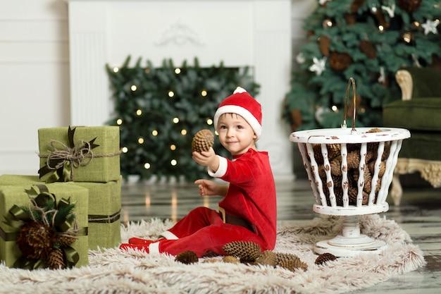 クリスマスツリーを飾るためにコーンで床で遊ぶかわいい幼児の肖像画。クリスマスツリーとクリスマスプレゼントの箱の近く。メリークリスマスとハッピーホリデー Premium写真
