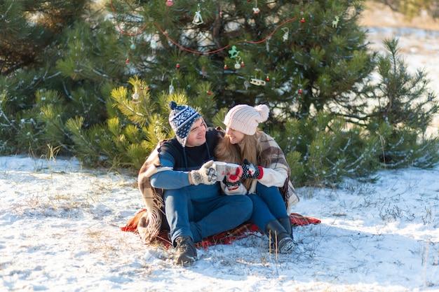 愛の若いカップルは、マシュマロと一緒に温かい飲み物を飲み、冬の森に座って、暖かく快適なラグに隠れて、自然を楽しみます。彼らは森で熱い飲み物を飲みながら話し、笑います Premium写真