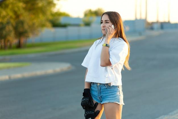 物思いに沈んだ顔をして携帯電話で話しているスポーツグローブの若い女性スケートボーダー Premium写真