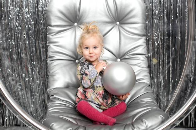 少女は椅子で銀のボールとガラスのボウルを果たしています。雪の女王カバー Premium写真
