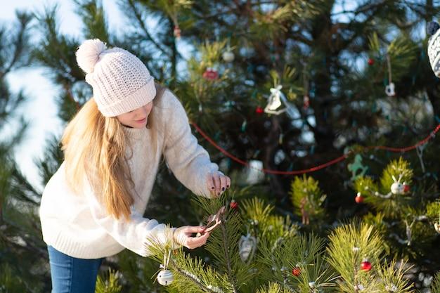 女の子は装飾的なおもちゃで飾って、森の冬の路上で緑の木を花輪します。 Premium写真