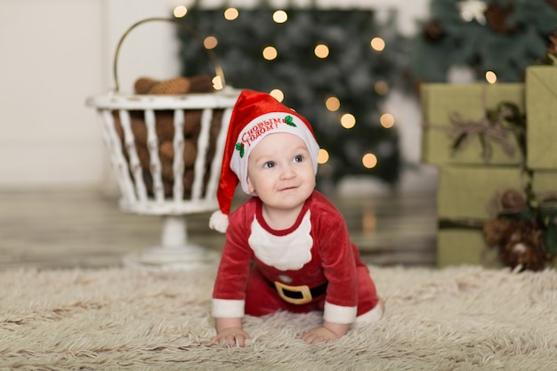 クリスマスツリーを飾るためにコーンで床で遊ぶかわいい幼児の肖像画。 Premium写真