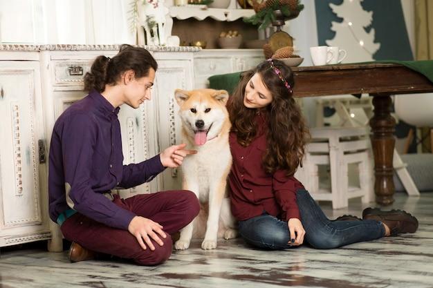 陽気な若いカップルがハグし、秋田犬の犬の犬にキス Premium写真