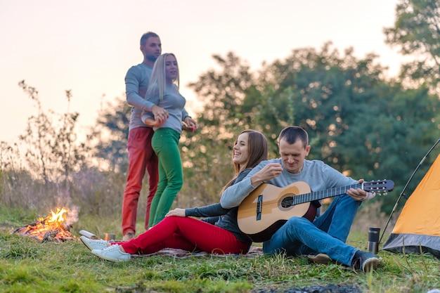 Группа счастливых друзей с гитарой, веселиться на свежем воздухе, возле костра и туристической палатки, кемпинг веселая счастливая семья Premium Фотографии
