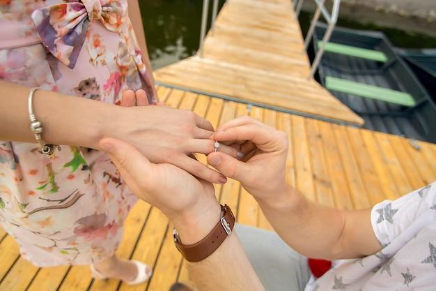 若いかわいい男は、木製の桟橋で彼の膝の上に立って、彼の最愛の女の子に結婚提案をします。木製の桟橋でのロマンスと愛。 Premium写真