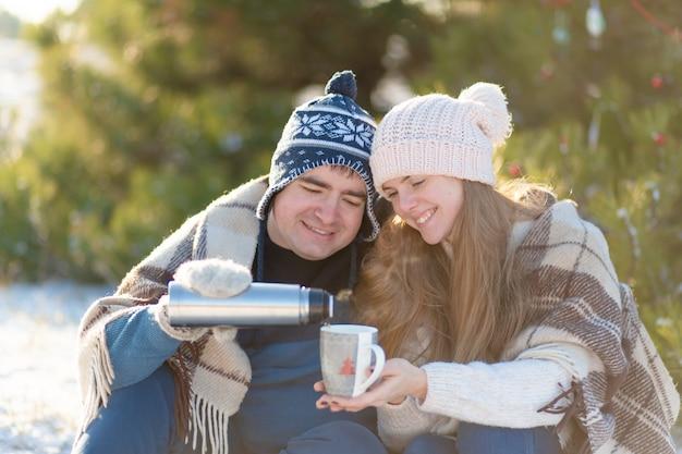 愛の若いカップルは、魔法瓶から温かい飲み物を飲む、森の中の冬に座って、暖かいに隠れて Premium写真