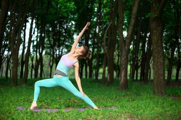 細いブルネットの少女はスポーツをし、夏の公園で美しく洗練されたヨガのポーズを実行します。緑豊かな森林。ヨガのマットの上の演習を行う女性 Premium写真