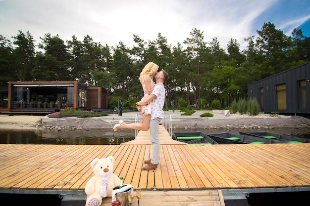 愛する若いカップルが木製の桟橋でキスします。桟橋のラブストーリー Premium写真