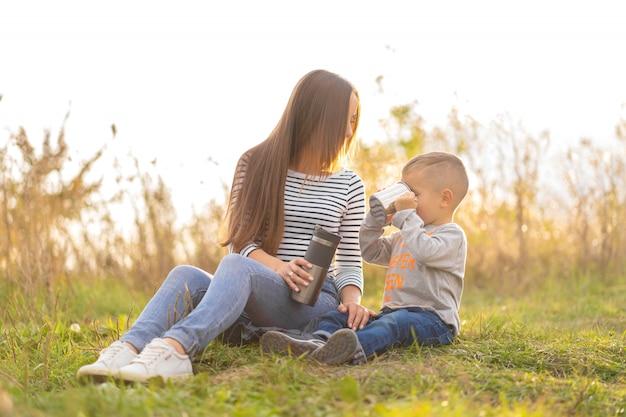 秋の散歩に幸せな家族。幼い息子を持つ若い美しい母親は、自然を楽しむ Premium写真