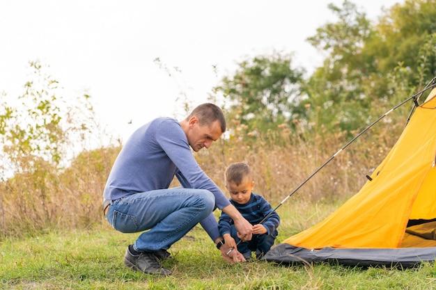 幼い息子と幸せな家族は、キャンプテントを設定します。幸せな子供時代、両親とのキャンプ旅行。子供がテントの設置を手伝います Premium写真