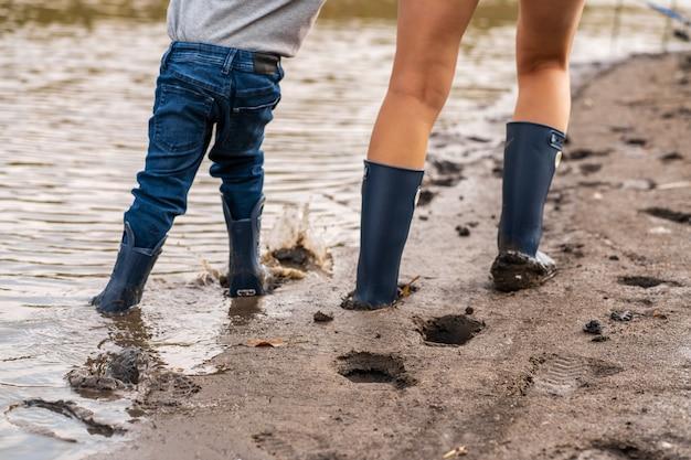 小さな息子とママはゴム長靴で湖の砂浜に沿って歩きます。都会から離れた自然の中で子どもたちと過ごす Premium写真