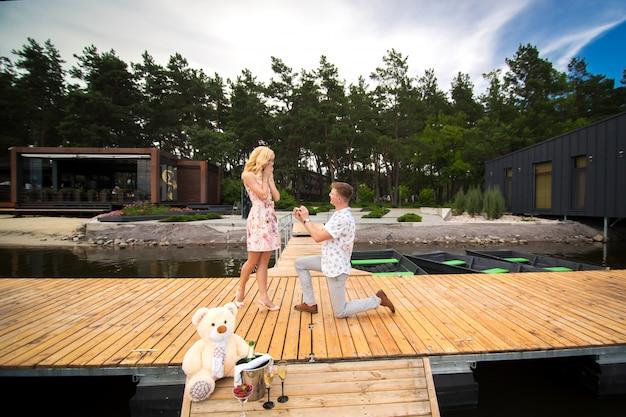 若いかわいい男は、木製の桟橋で彼の膝の上に立って、彼の最愛の女の子に結婚提案をします。木製の桟橋でのロマンスと愛 Premium写真