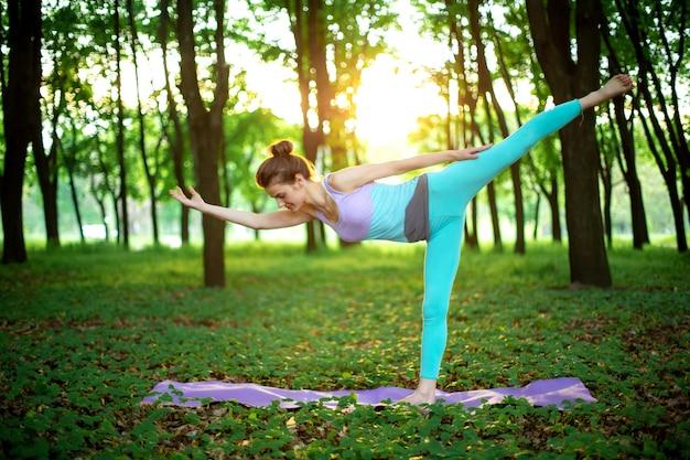 若いスポーツ少女は、やめられた緑の夏の森、ヨガのアサンの姿勢でヨガを練習します。瞑想と自然との一体感 Premium写真