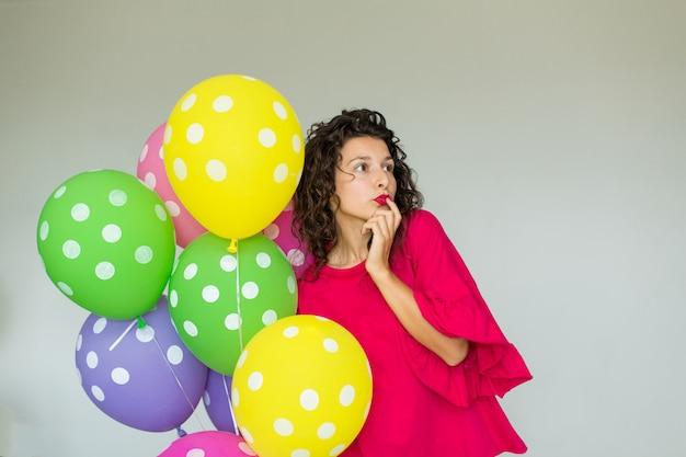 色の風船を持つ美しいかわいい陽気な女の子。休日の誕生日。 Premium写真